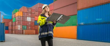 A female docker with folder in protective gear in a container handling area Stok Fotoğraf