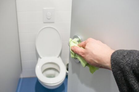 a hand cleans the door handle on a public toilet with a cloth