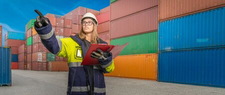 A female docker in protective gear in a container handling area