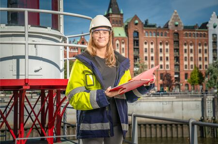 a female apprentice holding a clipboard in front of city background
