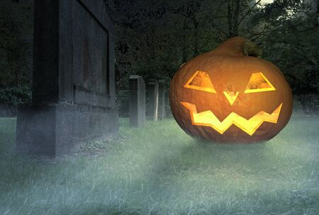 a scary grinning halloween pumpkin lies on a cemetery 스톡 콘텐츠