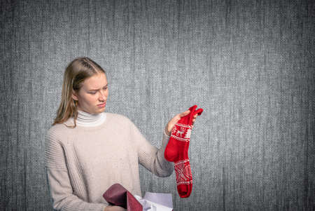 a young woman looks at her Christmas present and is unhappy Archivio Fotografico