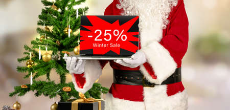 santa claus holds laptop in hand with 25 percent winter sale advertising