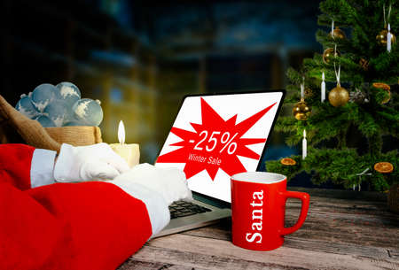 santa is checking 25 percent winter sale advertising on laptop