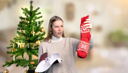 a woman in front of a Christmas tree is disappointed about her Christmas gift