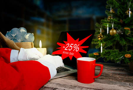 santa claus is checking 25 percent winter sale advertising on laptop in his workshop