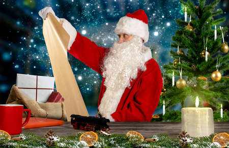 Santa Claus checks the wish list for the gifts in his workshop