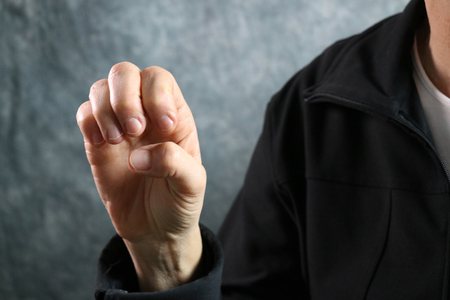 American Sign Language (ASL) letter E held in correct position next to body