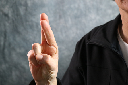 American Sign Language (ASL) letter R held in correct position next to body