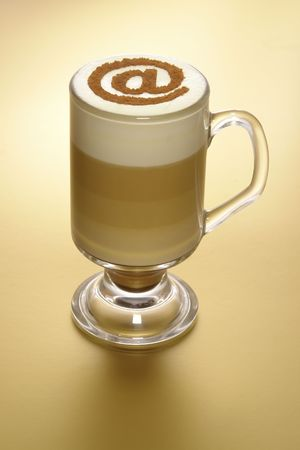 Coffee with milk, in glass with sign @, on golden back ground                             photo