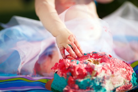 Cake smash aftermath. Baby pink two-tier birthday cake smashed by a one-year-old. Shabby fabric streamers blurred in the background. Banque d'images