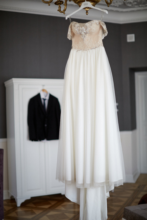 bridal gown: Bridegroom dress and bridal gown hanging in wardrobe