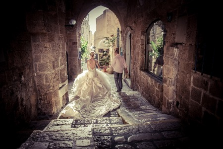 stroll: Beautiful pair of newlyweds enjoy a stroll through the streets of the old town of Tivoli, Italy, on their wedding day Stock Photo