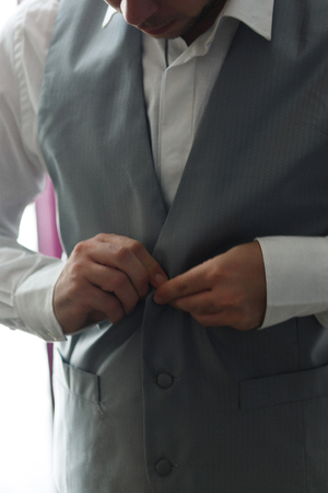 dressing up: Businessman buttons gray vest. Elegant man  or groom dressing up
