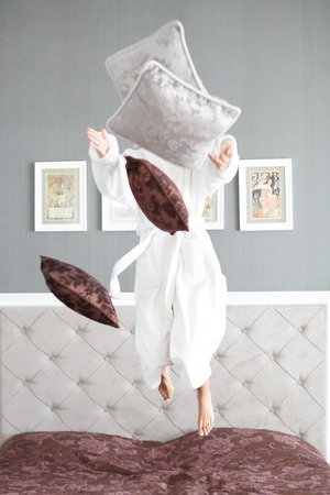 rushes: Young beautiful woman in a hotel room, jumping on the bed , full of vitality and energy, and rushes gray and brown pillows