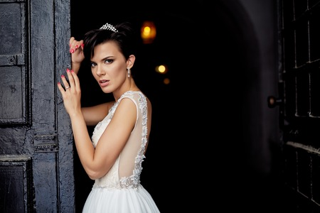 young wife: Beautiful bride in white dress posing near old wooden door