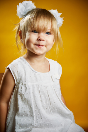 pity: Adorable little blonde girl in a white dress . The girl was only three years-Isolated on yellow background Stock Photo