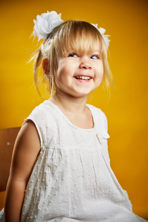 little blonde girl: Adorable little blonde girl in a white dress . The girl was only three years-Isolated on yellow background Stock Photo