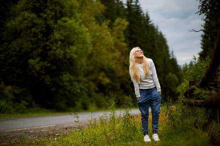 Beautiful blonde on a background of blue sky. Beautiful girl enjoying the nature. Breathing the fresh mountain air Stock Photo