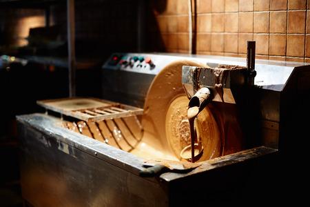 chocolatería: flujo de chocolate con leche caliente o corriente en la fábrica Foto de archivo