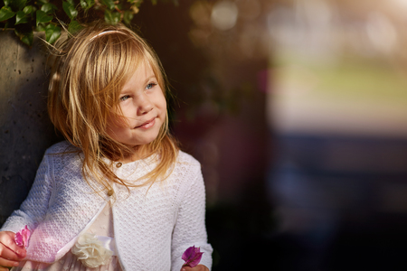 Beautiful little girl with bows smiling and looking up, outdoor portrait