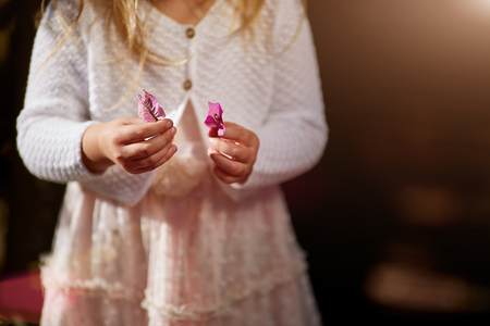 solar flare: child, hands close-up, flowers, white sweater a solar flare Stock Photo