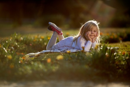 Portrait of a smiling little girl lying on green grass. Cute four years old child enjoying nature outdoors. Healthy carefree kid playing outside in summer park Stock Photo
