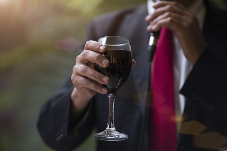 mans hand with a glass of red wine