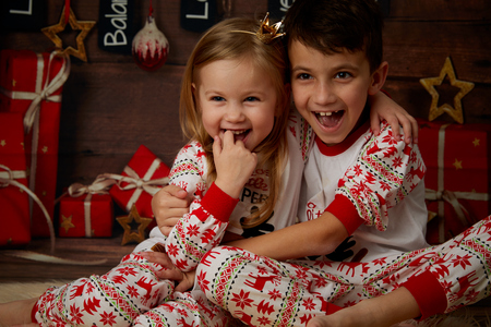 fireplace living room: Children in pajamas on the background of gifts