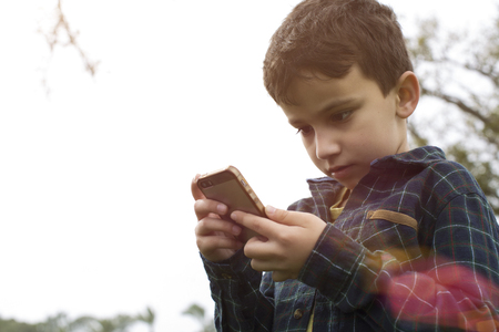 A young boy outside playing Pokemon Go on a iphone 新聞圖片