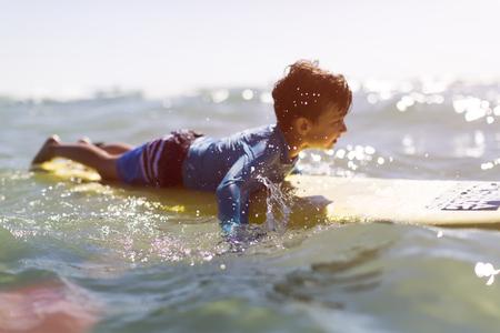 金髪の少年がテル ・ アビブでサーフィンの練習