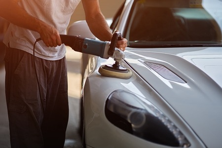 Car detailing series : Worker waxing white car Stock Photo