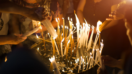 people lights a candle in the Church of the Holy Sepulchre in Jerusalem