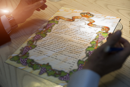 jewish groom signing a ketubah at his wedding