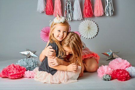Two cute young sisters posing together in a studio. Vertically framed shot isolated against a gray studio background. The older sister is hugging the younger one. Both are smiling at the camera Stock Photo
