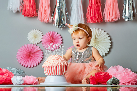 Baby girl and her birthday cake doing a smash cake in a studio Stock Photo