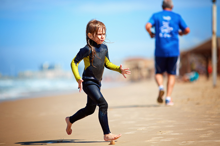 A girl in a surf suit runs out of the water