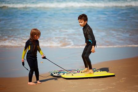Happy small kids having fun at tropical beach
