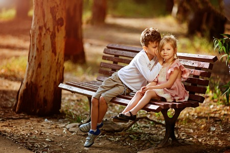 A cute boy shares a secret With his younger sister. Stock Photo