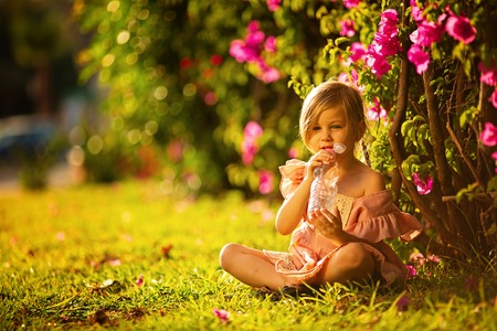 Cute little girl drinking water in a summer garden Stock Photo