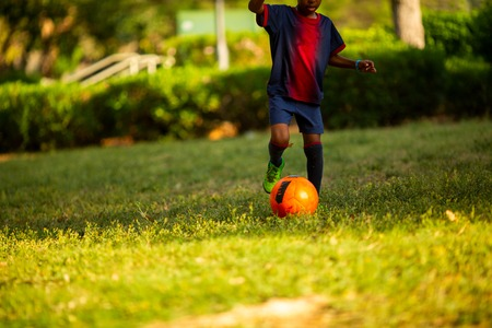 Close up of teenager's legs with a ball on football pitch. Cropped shot of soccer player training on the artificial grass field. Stock Photo