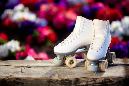 white female skates on the background of flowers
