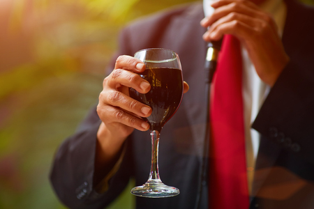 Rabbi holds kiddish cup with wine in front of Groom and Bride Stock Photo