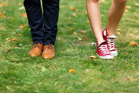 female legs in red sneakers and male legs in brown shoes Stock Photo
