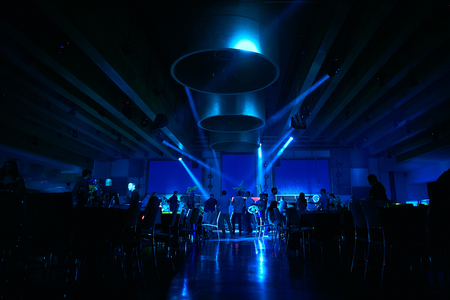 Dancing people in an underground club, blue stage light. Stock Photo