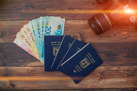 Stack of Israeli money bills in the amount of 200 shekels and an Israeli passport on a wooden table Stock Photo - 104145829