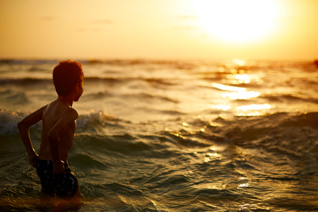 Boy looking out towards the sunset with the waves on there way in