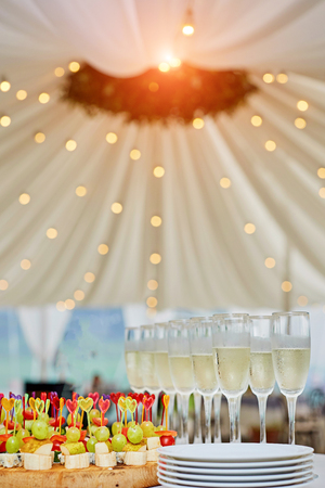 lot of different snacks, sandwiches and glasses with champagne on the table. A party. Stock Photo