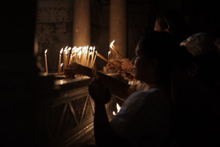 Jerusalem, Israel - June 06, 2018: Prayers lighting candles in the Holy Sepulchre Church in Jerusalem. The Holy Sepulchre Church is the most sacred place for all Christians in the world.