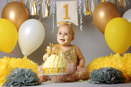 little girl with brown eyes with a bandage on her head and a beautiful dress crawling on the floor next to balloons and a cake marking her first birthday. Imagens